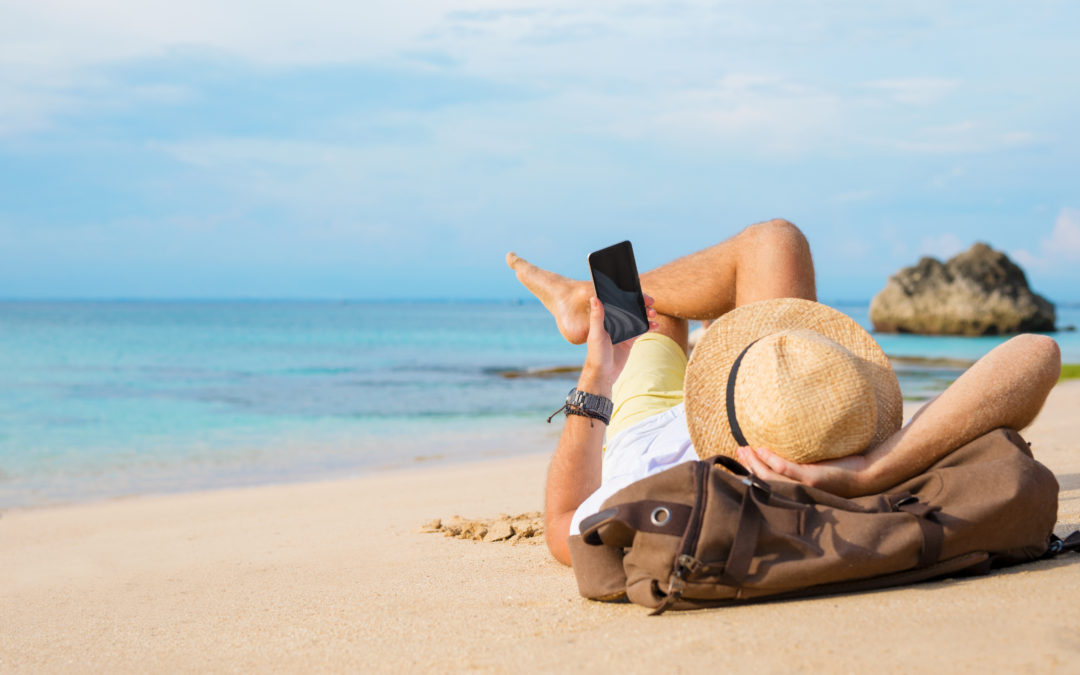 Guy with smartphone lying on the beach passive income